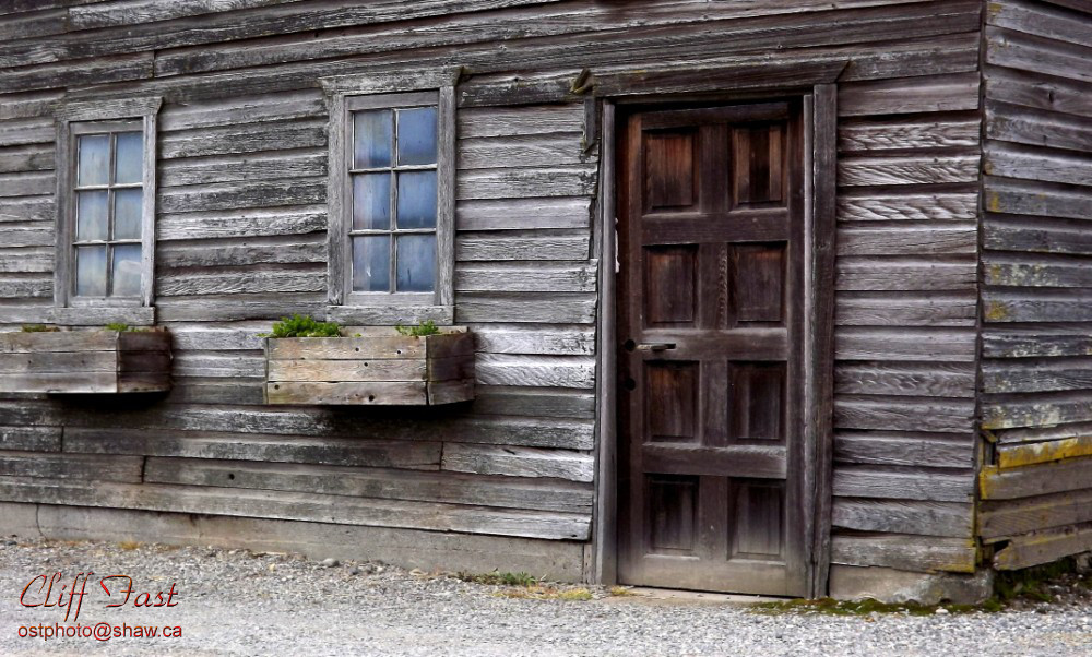 An example of a very old wooden structure with wooden window frames and a wooden door