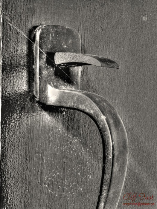 A door latch in B&W with a spider web