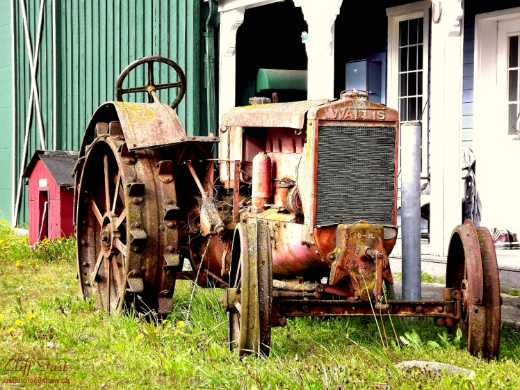 "An antique tractor. Built by the ""Wallis Company"""