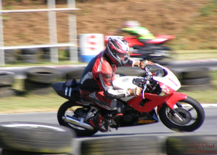 A panned shot of a motocycle on a racetrack.