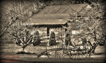 An old piece of farm equipment sitting in front of a shed.