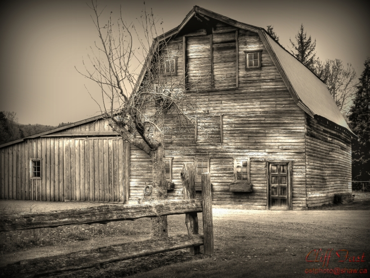 An old hip roofed barn and a split post fence.