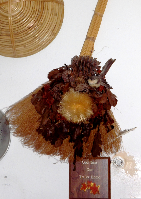 A stram broom fall ornament with the little bird perched in it where it belongs